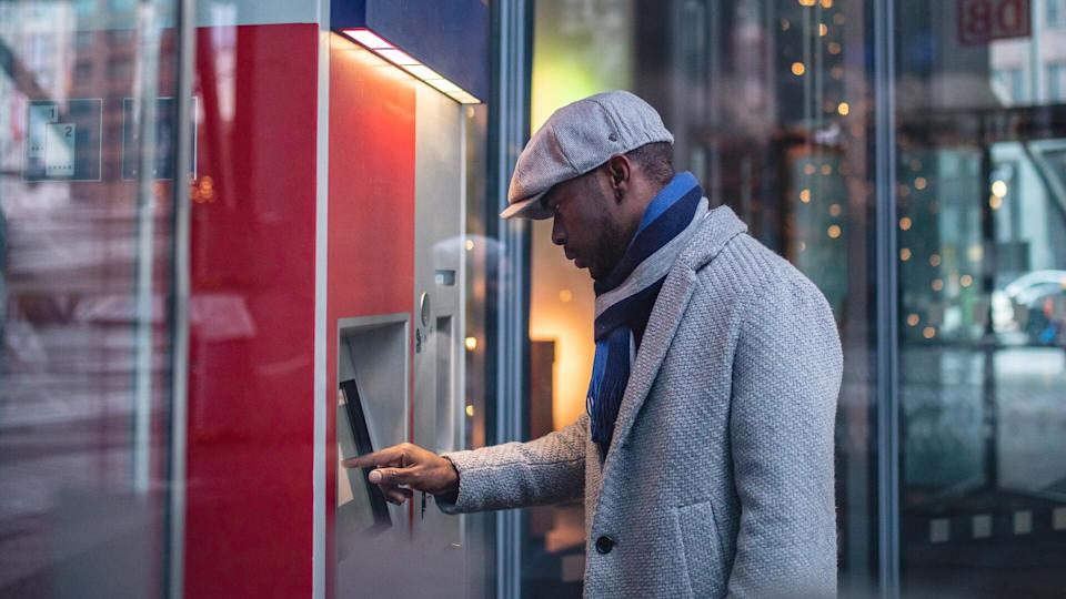 Handsome and beautiful black businessman using a ATM machine in the city.