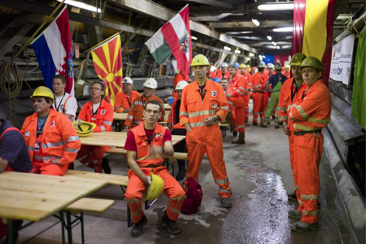 """Miners wait prior to the tunnel drilling machine """"Sissi"""" breaks through the last section of the Gotthard Base Tunnel near Faido in the canton of Tessin, Switzerland, Oct. 15, 2010. With 57 kilometers (35-miles) the new St. Gotthard tunnel is the world's longest tunnel. The 13.157 billion Swiss franc (9.6 billion euros, 13.6 billion US dollars) Alptransit project, which is due to be operational in 2017, constitutes the center piece of the New Railway Link through the Alps. Engineers are expected to start up the massive drilling machine - nicknamed Sissi - at 2 p.m. (1200 GMT; 8 a.m. EDT) so it can chew through the last remaining rock separating the two ends of the 57-kilometer (35.4-mile) Gotthard Base Tunnel."""