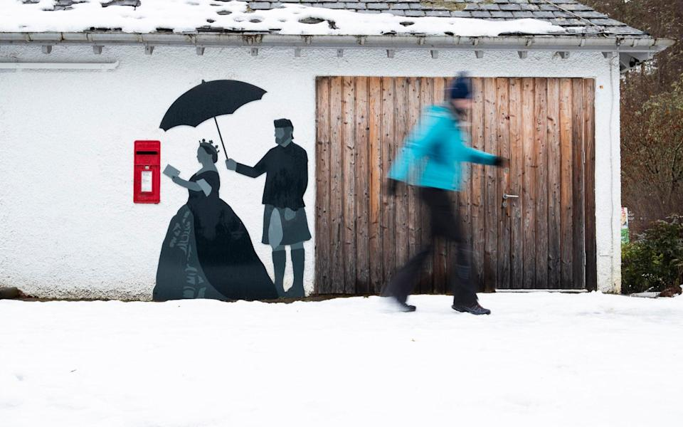 Snow surrounds the post box at Queen's View, which features the silhouette of Queen Victoria and her Scottish servant John Brown alongside on the wall, near Pitlochry, Perthshire, on Thursday - Jane Barlow/PA