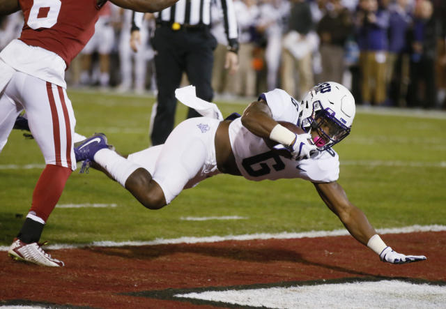 "TCU running back <a class=""link rapid-noclick-resp"" href=""/ncaaf/players/264359/"" data-ylk=""slk:Darius Anderson"">Darius Anderson</a> (6) dives into the end zone for a touchdown in front of Oklahoma defender Tre Brown, left, in the first quarter of an NCAA college football game in Norman, Okla., Saturday, Nov. 11, 2017. (AP Photo/Sue Ogrocki)"