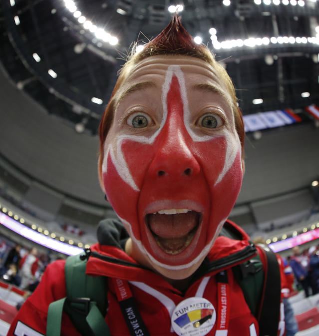 Canadian hockey fan Evalyn Collinge shows off the Canadian maple leaf painted on her face before the men's gold medal ice hockey game against Sweden at the 2014 Winter Olympics, Sunday, Feb. 23, 2014, in Sochi, Russia. (AP Photo/Julio Cortez)