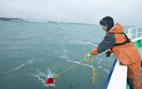 Kaori Suzuki, manager of NPO Tarachine, casts a bucket into the Pacific Ocean to collect seawater samples about a mile from the Fukushima No. 2 Nuclear Power Plant - Credit: Simon Townsley