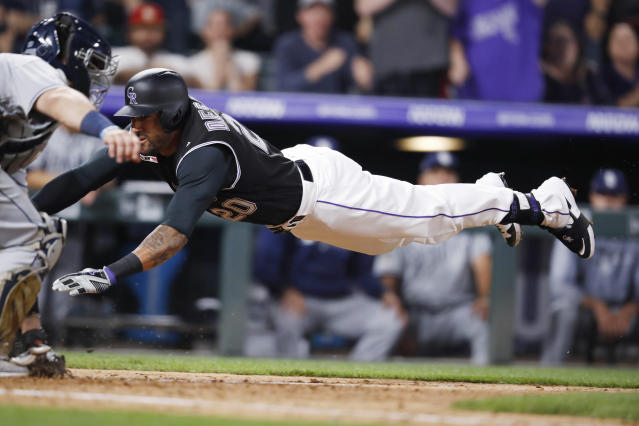 Colorado Rockies' Ian Desmond, right, dives into home plate as San Diego Padres catcher Austin Hedges catches the throw during the sixth inning of a baseball game Friday, June 14, 2019, in Denver. Desmond hit a three-run, inside-the-park home run. (AP Photo/David Zalubowski)