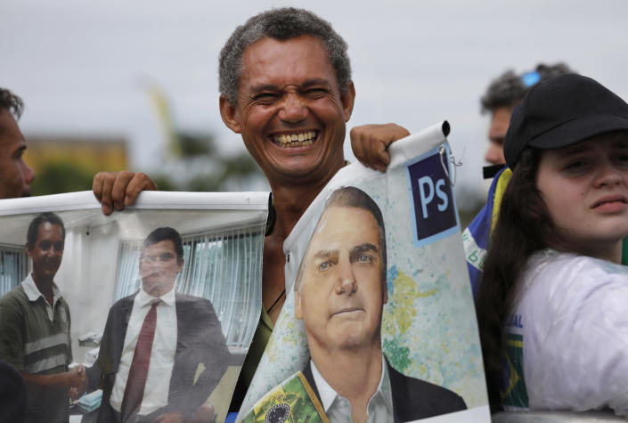 A supporter holds a photo of Brazil's former army captain Jair Bolsonaro before the swearing-in ceremony in front of the Planalto palace in Brasilia, Brail, Tuesday Jan. 1, 2019. Once an outsider mocked by fellow lawmakers for his far-right positions, constant use of expletives and even casual dressing, Bolsonaro is taking office as Brazil's president Tuesday. (AP Photo/Silvia Izquierdo)