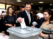 FILE - This April 13, 2016 file photo released on the official Facebook page of Syrian Presidency, shows Syrian President Bashar Assad casting his ballot in the parliamentary elections, as his wife Asma, left, stands next to him, in Damascus, Syria. For fifty years, the Assad family has controlled Syria, overseeing transformations, modernization, uprisings and upheaval while becoming among the most divisive figures of their time. (Syrian Presidency via AP, File)