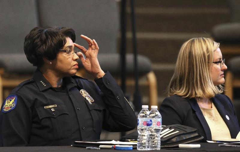 Phoenix Police Chief Jeri Williams, left, and Mayor Kate Gallego, right, listen to a speaker at a community meeting, Tuesday, June 18, 2019, in Phoenix. The community meeting stems from reaction to a videotaped encounter that surfaced recently of Dravon Ames and his pregnant fiancee, Iesha Harper, having had guns aimed at them by Phoenix police during a response to a shoplifting report, as well as the issue of recent police-involved shootings in the community. (AP Photo/Ross D. Franklin)