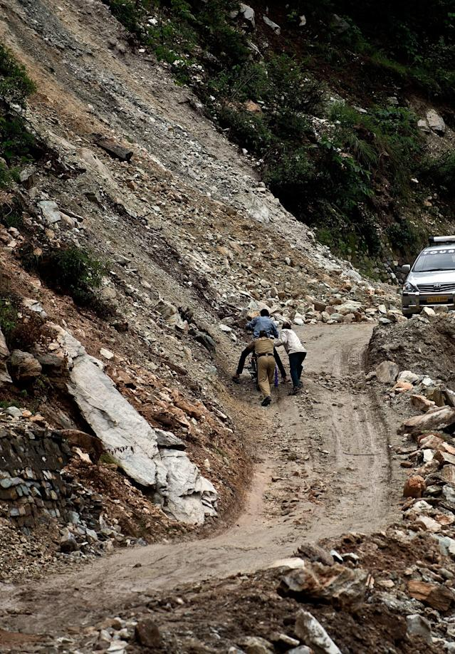 Indian worker and a policeman push a motorcyclist on a damaged section of road between Rudraprayag and Gauchar, at Gauchar on June 25, 2013, after flash flooding hit the northern Indian state of Uttarakhand. Some 1000 people have been killed in flash floods and landslides in northern India, as a top official warned that rebuilding of the devastated Himalayan region would take years. AFP PHOTO/MANAN VATSYAYANA