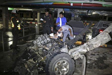 Police officers inspect the site of a car bomb blast at a car park of a shopping mall on the Thai tourist island of Koh Samui April 10, 2015. REUTERS/Dailynews Newspaper