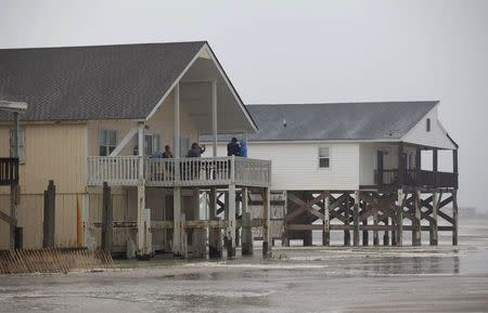 Tourists take photos of the surf from their beach houses during Hurricane Arthur, on the west end of Ocean Isle Beach, North Carolina July 3, 2014. REUTERS/Randall Hill
