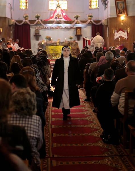 A nun walks as worshipers attend a Christmas mass at the Mother Teresa Catholic Church in Basra, Iraq's second-largest city, 340 miles (550 kilometers) southeast of Baghdad, Iraq, Wednesday, Dec. 25, 2013. Militants on Wednesday launched two separate attacks against Christians in Baghdad, killing more than a dozen people, officials said. (AP Photo/Nabil al-Jurani))