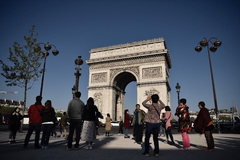Tourists returned to the Champs Elysees on Friday, with many vowing that the killing of a policeman on the world-famous avenue would not stop them from coming