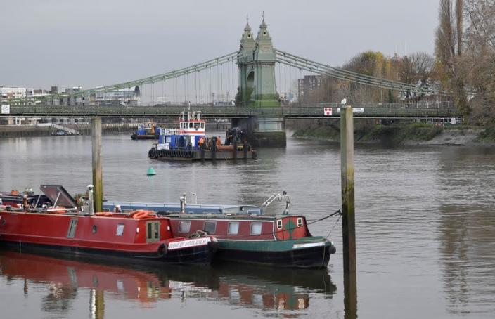 Houseboats are seen moored near Hammersmith Bridge, the closure of which has caused the annual Oxford versus Cambridge boat race on the River Thames to be relocated, London, Britain