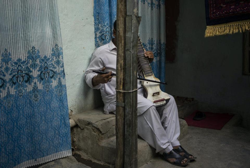 """<span class=""""caption"""">An Afghan musician poses for a portrait with his dilruba in Kabul, Afghanistan, on Sept. 18, 2021. About a month after the Taliban seized power in Afghanistan, the music is starting to go quiet.</span> <span class=""""attribution""""><span class=""""source"""">(AP Photo/Bernat Armangue)</span></span>"""