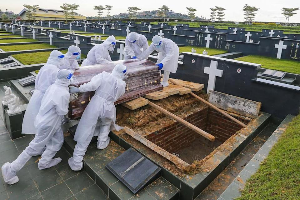 Workers wearing personal protective equipment (PPE) carry a coffin containing a body of a person who died from the Covid-19 disease at the Christian cemetery at Fairy Park in Klang June 6, 2021. — Picture by Yusof Mat Isa