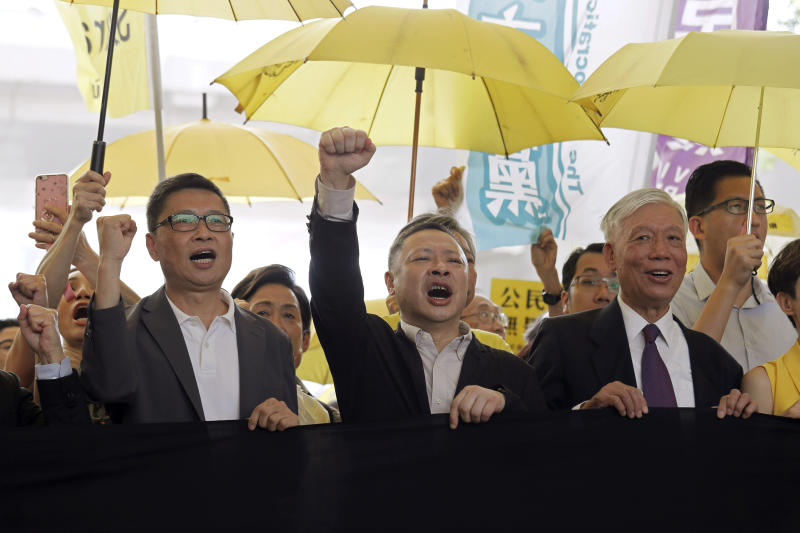 Occupy Central leaders, from left, Chan Kin-man, Benny Tai and Chu Yiu-ming chant slogans before entering a court in Hong Kong, Wednesday, April 24, 2019. The court is preparing to sentence nine leaders of massive 2014 pro-democracy protests convicted last month of public nuisance offenses. The sentences to be handed down Wednesday are seen as an effort by the government of the semi-autonomous Chinese territory to draw a line under the protests. (AP Photo/Kin Cheung)