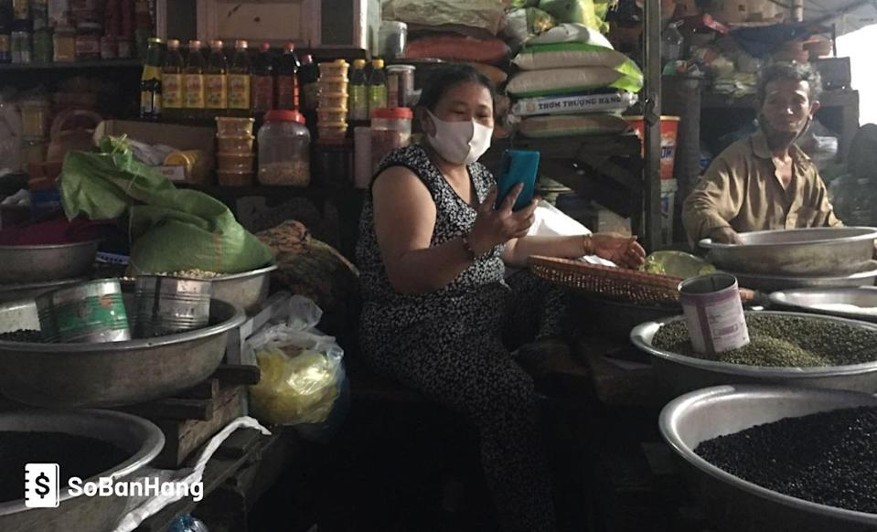 A photo of a merchant in Vietnam looking at a smartphone