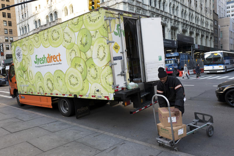 FILE - In this Nov. 27, 2017, file photo a FreshDirect driver loads boxes into his truck in New York. Grocery delivery services are growing rapidly, but shoppers need to decide if the convenience is worth the higher cost. Big companies like Amazon and Walmart are expanding grocery delivery, as are regional players like FreshDirect. (AP Photo/Mark Lennihan, File)