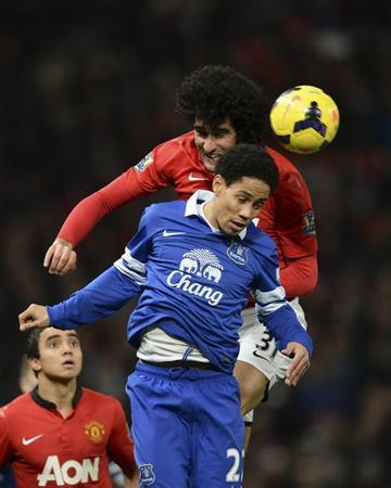Manchester United's Marouane Fellaini (top) challenges Everton's Steven Pienaar during their English Premier League soccer match at Old Trafford in Manchester, northern England December 4, 2013. REUTERS/Nigel Roddis