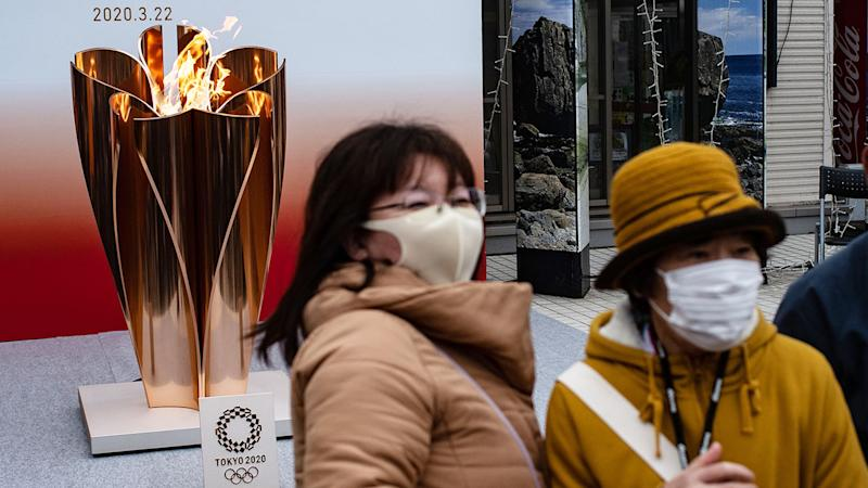 Seen here, locals in Tokyo pose next to the Olympic torch wearing face masks.