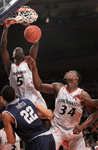 Cincinnati's Justin Jackson, top, slams the ball over Yancy Gates, right, and Georgetown's Otto Porter during the quarterfinal round of the Big East NCAA college basketball conference tournament in New York, Thursday, March 8, 2012. (AP Photo/Seth Wenig)