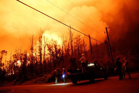 Journalists and National Guard soldiers watch as lava erupts in Leilani Estates