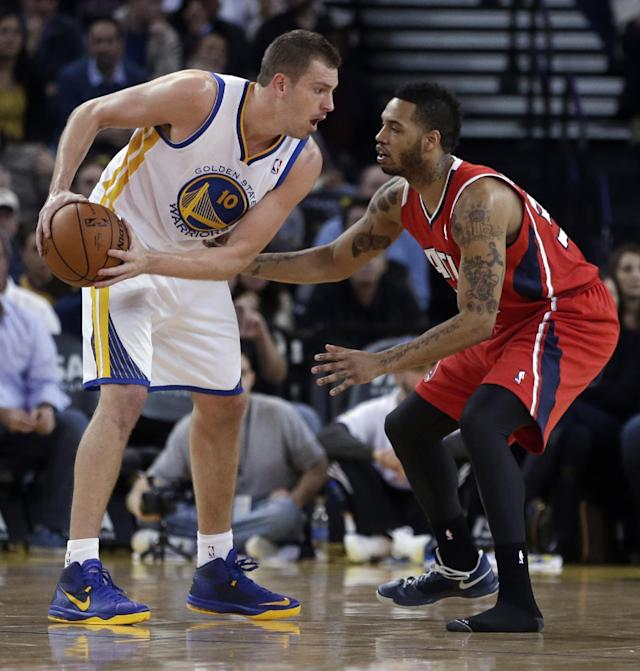 Atlanta Hawks' Mike Scott, right, missing his left shoe, guards Golden State Warriors' David Lee (10) during the first half of an NBA basketball game Friday, March 7, 2014, in Oakland, Calif. (AP Photo/Ben Margot)