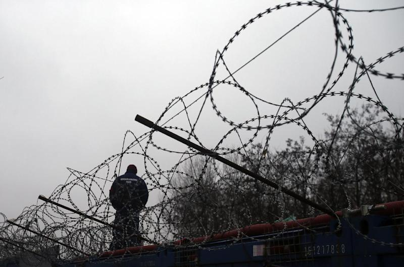 """A Hungarian police officer stands guard at Serbia's border with Hungary near a makeshift camp for migrants in Horgos, Serbia, Wednesday, Feb. 8, 2017. European Commission Vice-President Frans Timmermans said Wednesday that it is """"highly urgent"""" for countries to live up to their pledges, with the legally binding scheme set to expire in September. (AP Photo/Darko Vojinovic)"""