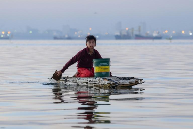 Every weekend, Reymark Cavesirano paddles out across Manila Bay on a makeshift raft of styrofoam to work helping fishermen clean their nets