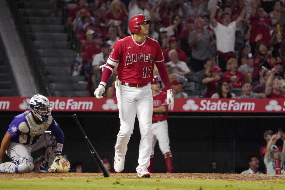 Los Angeles Angels' Shohei Ohtani, right, heads to first as he hits a two-run home run as Colorado Rockies catcher Elias Diaz watches during the sixth inning of a baseball game against the Colorado Rockies Tuesday, July 27, 2021, in Anaheim, Calif. (AP Photo/Mark J. Terrill)