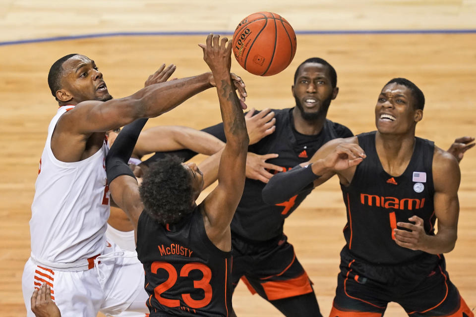 Clemson forward Aamir Simms, left, battles for a rebound with Miami guard Kameron McGusty (23) and teammates Anthony Walker, right, and Elijah Olaniyi, second from right, during the second half of an NCAA college basketball game in the second round of the Atlantic Coast Conference tournament in Greensboro, N.C., Wednesday, March 10, 2021. (AP Photo/Gerry Broome)
