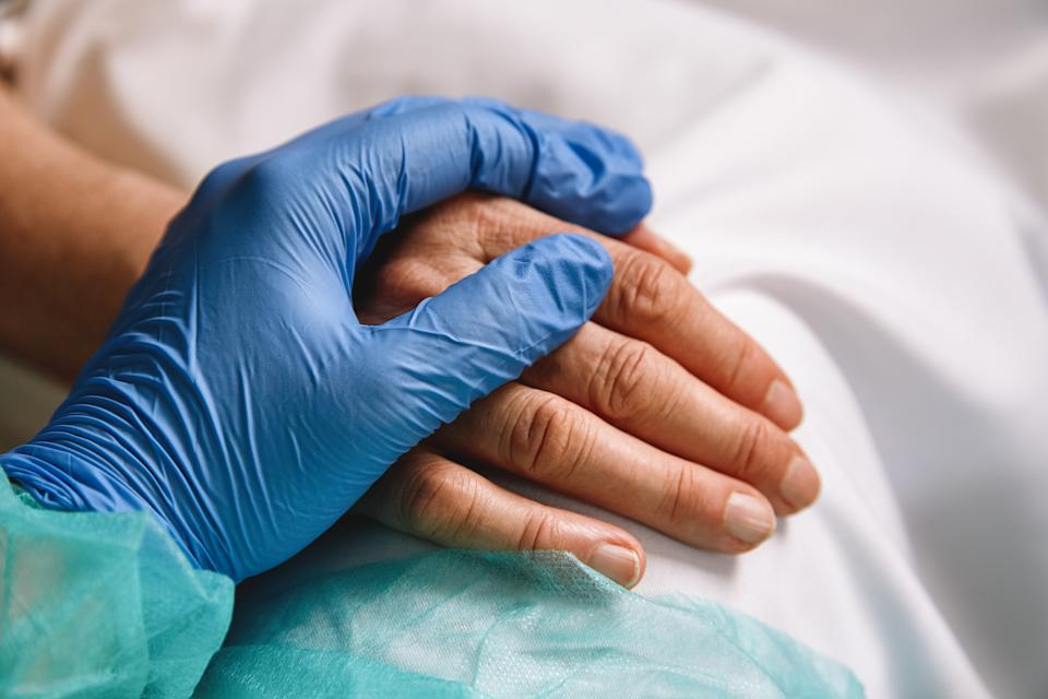 Close up of a doctor hand with blue glove giving support and love to a patient at hospital. Coronavirus pandemic concept.