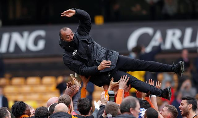 Wolves manager Nuno Espírito Santo is thrown into the air by his players as they celebrate the club's return to the Premier League after their game against Birmingham City.