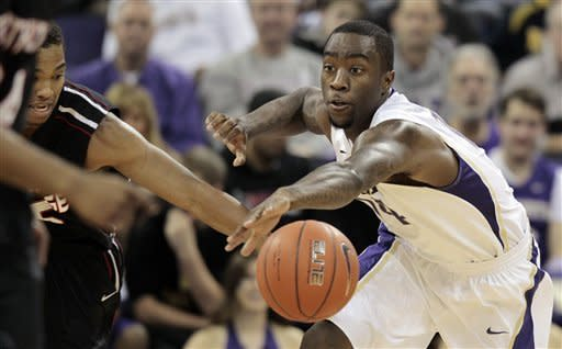 Washington's Tony Wroten, right, beats Cal State Northridge's Aqeel Quinn to a loose ball in the first half of an NCAA college basketball game Thursday, Dec. 22, 2011, in Seattle. (AP Photo/Elaine Thompson)
