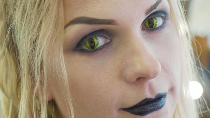Close-up portrait of young pretty woman with halloween makeup at beauty salon. Face of lady with cat eyes contact lenses.