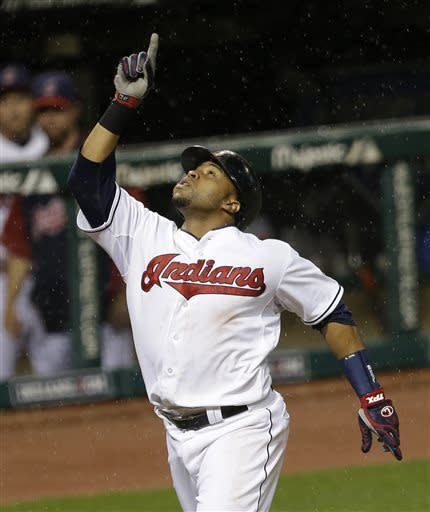 In the rain, Cleveland Indians' Carlos Santana points up as he runs the bases after hitting a two-run home run off Detroit Tigers starting pitcher Justin Verlander in the fifth inning of a baseball game onWednesday, May 22, 2013, in Cleveland. Indians' Michael Brantley also scored. (AP Photo/Tony Dejak)