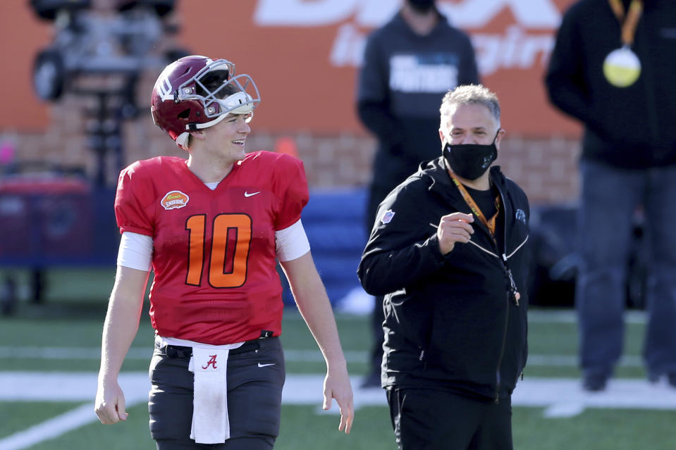 Quarterback Mac Jones of Alabama (10) shares a laugh with American Team head coach Matt Rhule (Carolina Panthers) during the American team practice for the NCAA college football Senior Bowl in Mobile, Ala, Thursday, Jan. 28, 2021. (AP Photo/Rusty Costanza)