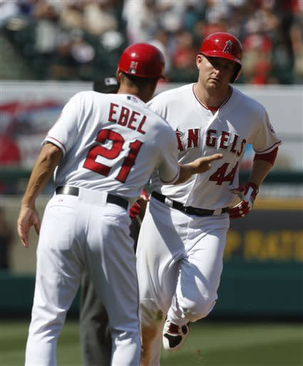 Los Angeles Angels designated hitter Mark Trumbo (44) is congratulated by third base coach Dino Ebel after hitting a two-run home run in the seventh inning of a baseball game against the Baltimore Orioles in Anaheim, Calif., on Saturday, May 4, 2013. (AP Photo/Christine Cotter)