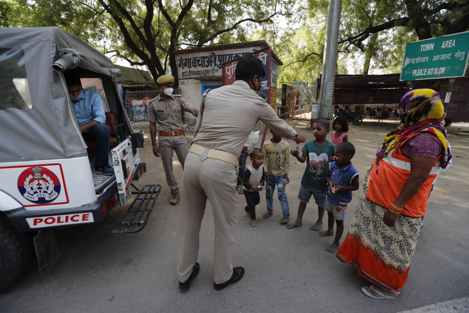 A policeman distributes tea during lockdown to prevent the spread of new coronavirus in Prayagraj, India, Saturday, April 25, 2020. As governments around the world try to slow the spread of the coronavirus, India has launched one of the most draconian social experiments in history, locking down its entire population, including an estimated 176 million people who struggle to survive on $1.90 a day or less. (AP Photo/Rajesh Kumar Singh)