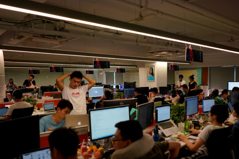 FILE PHOTO: Employees work at DingTalk office, an offshoot of Alibaba Group Holding Ltd, in Hangzhou