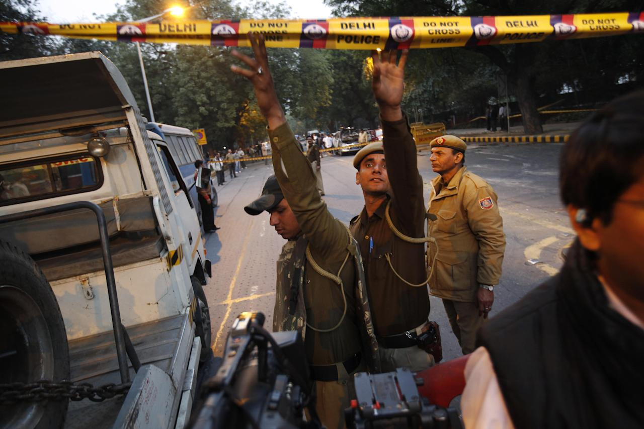 Indian policemen lift police tape for a vehicle after an explosion tore through a car belonging to the Israel Embassy, background, in New Delhi, India, Monday, Feb. 13, 2012. The wife of an Israeli diplomat was injured in the explosion , the same day as an Israeli Embassy staffer in Georgia found a bomb underneath his car, which was dismantled before exploding, according to Indian and Israeli media reports.(AP Photo/Kevin Frayer)
