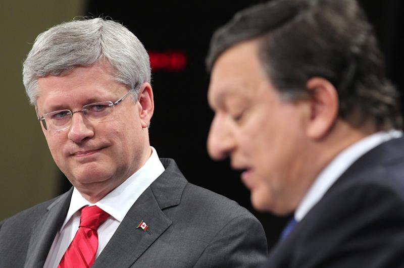Canada's Prime Minister Stephen Harper, left, looks at European Commission President Jose Manuel Barroso during a media conference at the European Commission headquarters in Brussels, Friday, Oct. 18, 2013. Canada and the European Union finalized a landmark free trade agreement to boost growth and employment in both economies. (AP Photo/Yves Logghe)
