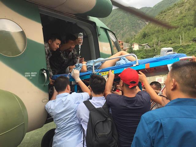 <p>Rescuers transfer a survivor, injured during an earthquake, by a helicopter to Sichuan Provincial People's Hospital in Jiuzhaigou in China's southwestern Sichuan province on Aug. 9, 2017. (Photo: STR/AFP/Getty Images) </p>