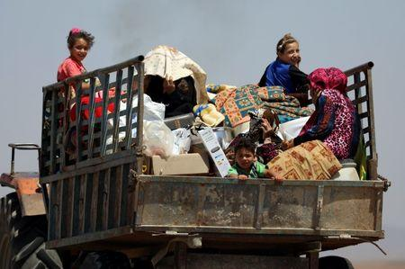People ride on a truck with their belongings in Deraa countryside, Syria June 22, 2018. REUTERS/Alaa al-Faqir