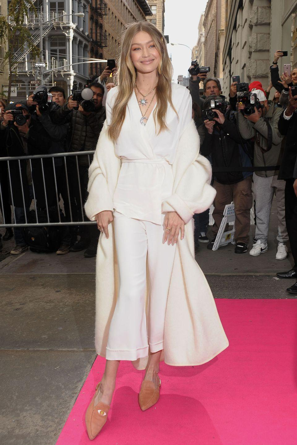 """<p>In a white wrap blouse and flared cropped trousers, a white mohair coat, layered necklaces, and her new <a href=""""https://www.harpersbazaar.com/fashion/models/a13143625/gigi-hadid-stuart-weitzman-mule/"""" rel=""""nofollow noopener"""" target=""""_blank"""" data-ylk=""""slk:Gigi Hadid x Stuart Weitzman mules"""" class=""""link rapid-noclick-resp"""">Gigi Hadid x Stuart Weitzman mules</a> at a launch event for the collab in NYC.</p>"""