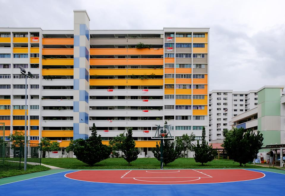 Colourful block of HDB flats (painted in white yellow orange blue) in yishun on bright, clear day, Singapore flags hung over some balconies. Neighbourhood park and basketball court in front.