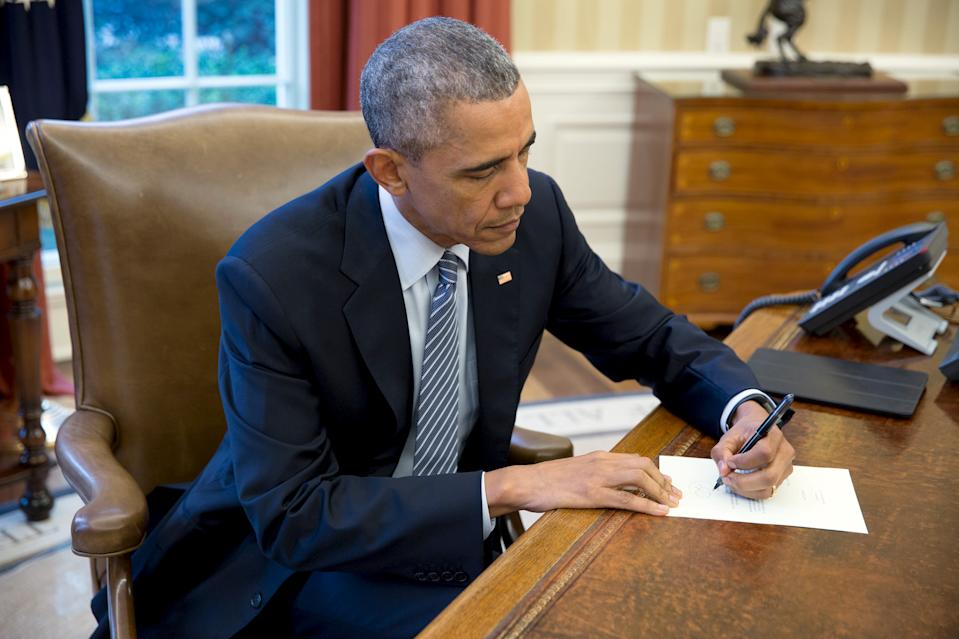 U.S. President Barack Obama signs a letter back to 76-year-old Cuban letter writer Ileana Yarza as he sits at his desk in the Oval Office of the White House in this official White House handout photo taken in Washington March 14, 2016 and released by the White House on March 17, 2016.  REUTERS/The White House/Pete Souza/Handout via Reuters  ATTENTION EDITORS - THIS PICTURE WAS PROVIDED BY A THIRD PARTY. REUTERS IS UNABLE TO INDEPENDENTLY VERIFY THE AUTHENTICITY, CONTENT, LOCATION OR DATE OF THIS IMAGE. FOR EDITORIAL USE ONLY. NOT FOR SALE FOR MARKETING OR ADVERTISING CAMPAIGNS. THIS PICTURE IS DISTRIBUTED EXACTLY AS RECEIVED BY REUTERS, AS A SERVICE TO CLIENTS.      TPX IMAGES OF THE DAY