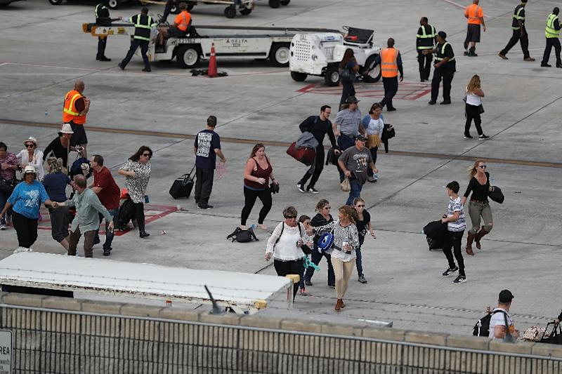 People seek cover on the tarmac of Fort Lauderdale-Hollywood International airport after a shooting took place near the baggage claim on January 6, 2017 in Fort Lauderdale, Florida (AFP Photo/JOE RAEDLE)