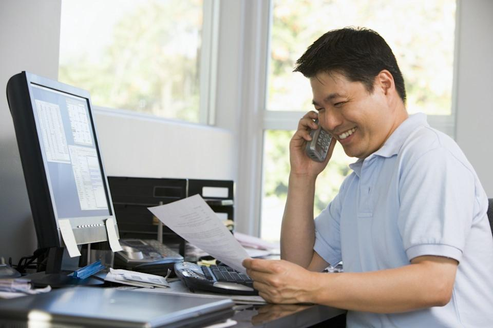 middle aged asian man looking at paperwork