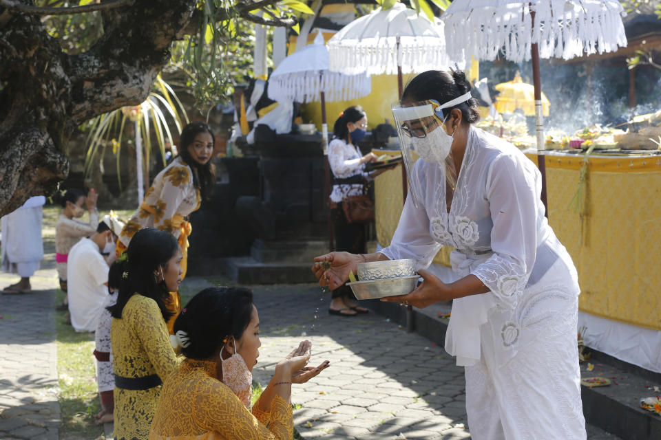 A Balinese woman wearing face shied and face mask gives holy water to a prayer at a temple amid concerns of the new coronavirus outbreak during a Hindu ritual in Bali, Indonesia Saturday, July 4, 2020. (AP Photo/Firdia Lisnawati)