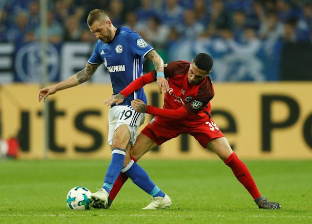 Soccer Football - DFB Cup - Schalke 04 vs Eintracht Frankfurt - Veltins-Arena, Gelsenkirchen, Germany - April 18, 2018 Schalke's Guido Burgstaller in action with Eintracht Frankfurt's Omar Mascarell REUTERS/Leon Kuegeler DFB RULES PROHIBIT USE IN MMS SERVICES VIA HANDHELD DEVICES UNTIL TWO HOURS AFTER A MATCH AND ANY USAGE ON INTERNET OR ONLINE MEDIA SIMULATING VIDEO FOOTAGE DURING THE MATCH.